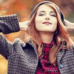 Attraktive rothaarige Frau im Herbstwald