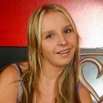 Blonde junge Frau sitzt auf dem Bett
