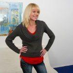 Blonde reife Frau im Wohnzimmer