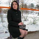 Junge Frau an der Bushaltestelle
