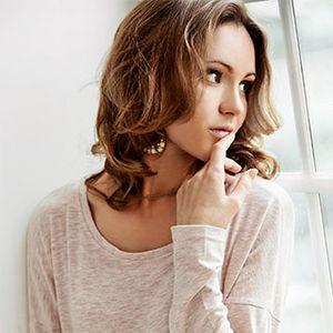Schüchterne junge Frau am Fenster